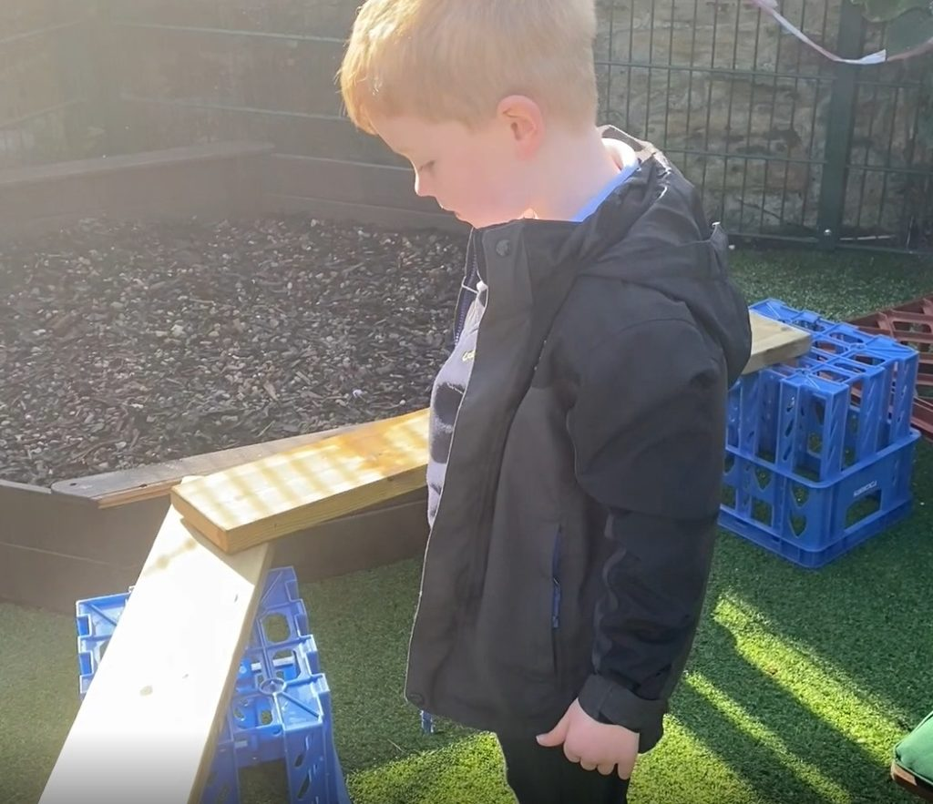 Little boy works out how to fix the problem with the balance beams.