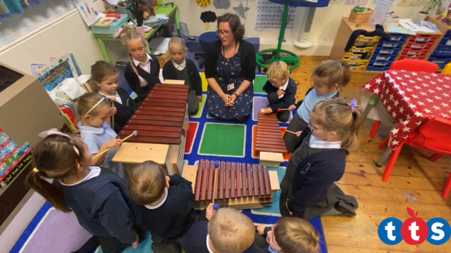 Class of children around three xylophones